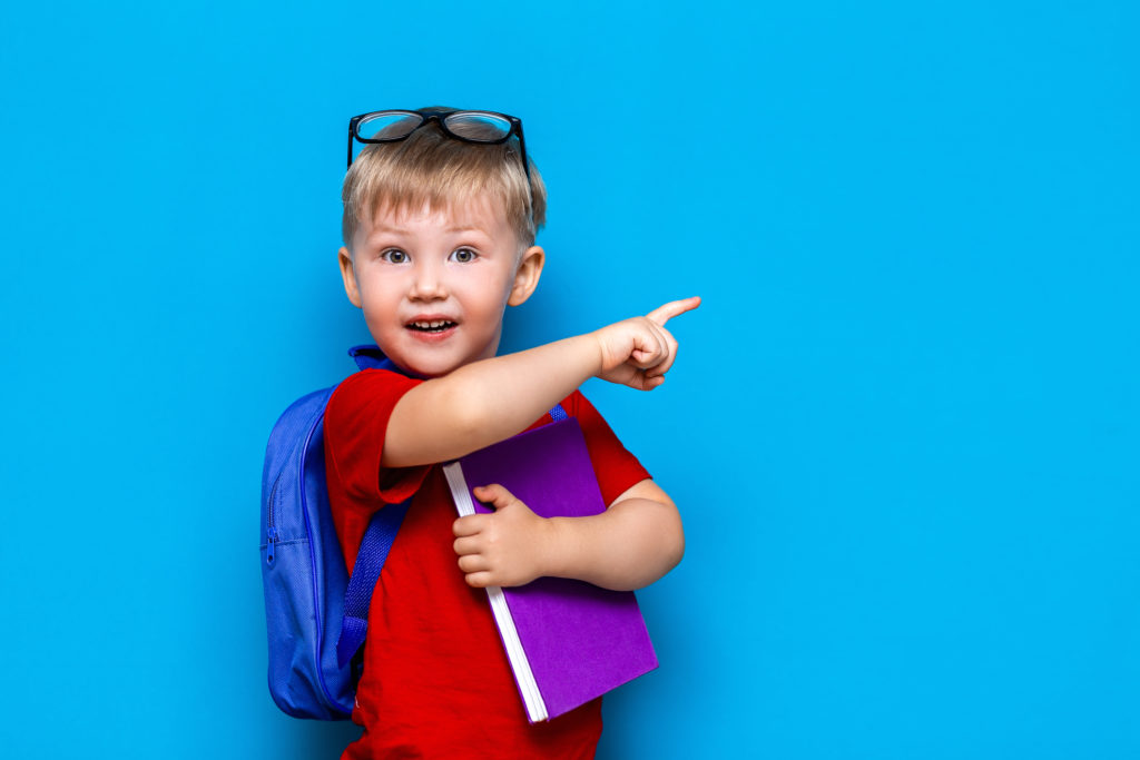 Back to school First grade junior lifestyle. Small boy in red t-shirt. Close up studio photo portrait of smiling boy in glasses with schoolbag and book show somethind with his finger.
