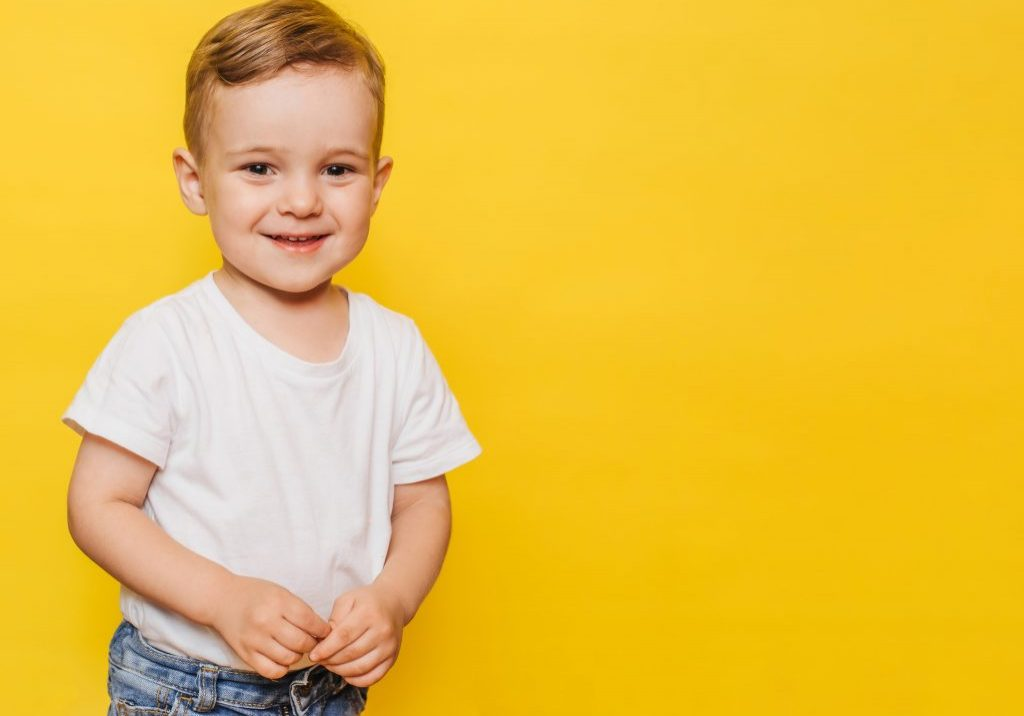 Portrait of a cute laughing little boy yellow background. Copy space.