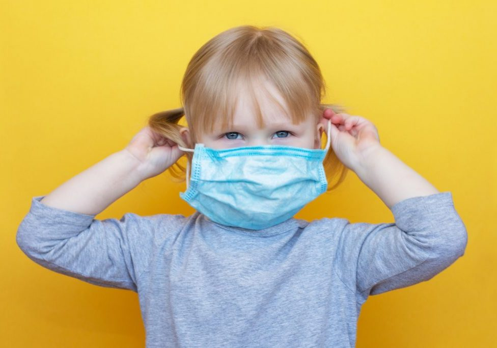Little caucasian girl dresses protective mask on yellow backgraund. Concept self-care. Prevention from the virus. Epidemic Precautions. The child is in quarantine.