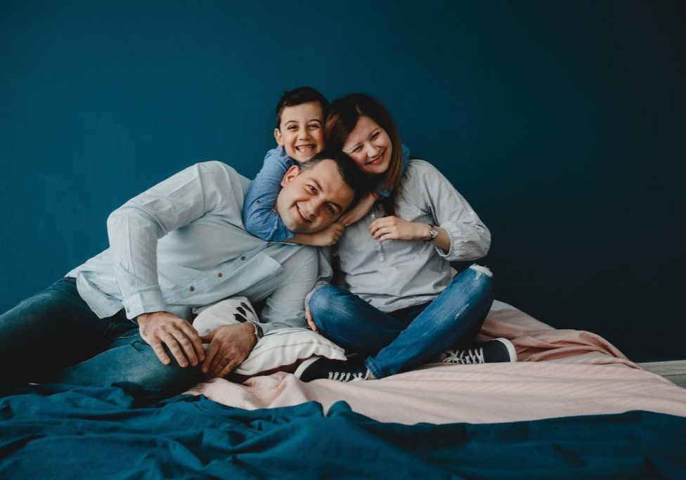 Young parents lie with their son on the bed