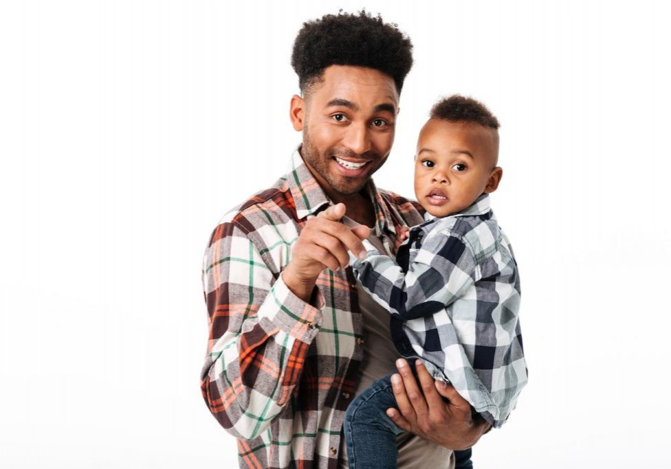 Portrait of a smiling young african man holding his little son while standing and pointing finger at camera isolated over white background