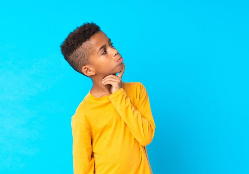 African American boy over isolated blue background having doubts and with confuse face expression