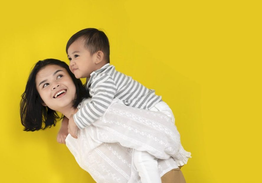 Mother and son hug, laugh and play together on yellow background. Happy family moments.